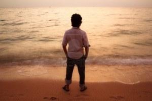 12669740-asian-man-standing-alone-watching-sunset